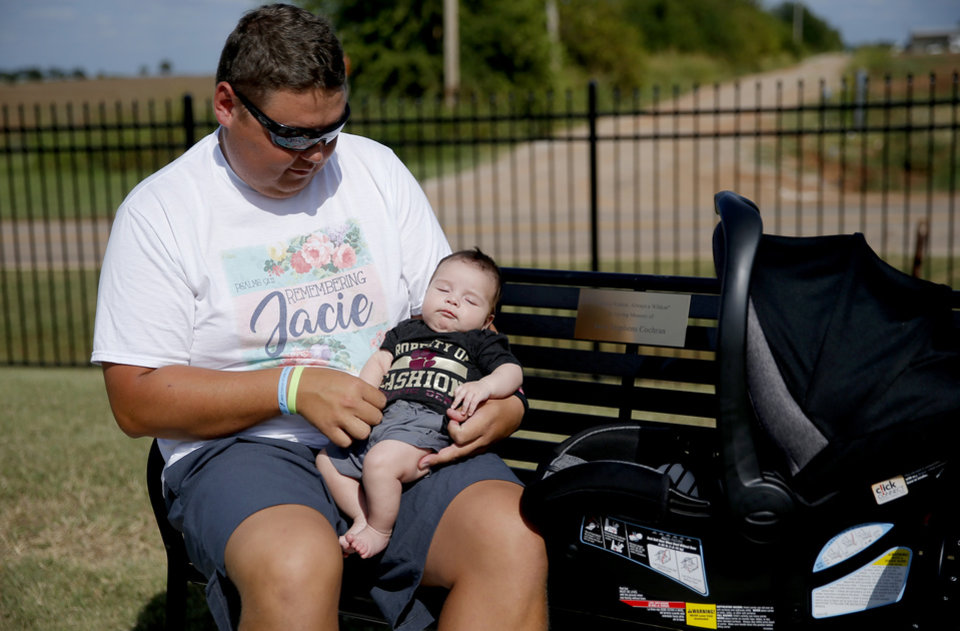 Photo - Cashion assistant coach Cale Cochran and his son Jaxon listen to music while sitting on a bench dedicated to his late wife Jacie Jacie Cochran before a high school football game between Cashion and Perry in Cashion, Okla., Friday, Sept. 4, 2020. Cochran's wife, Jacie, died July 2 shortly after giving birth to their son Jaxon. [Bryan Terry/The Oklahoman]