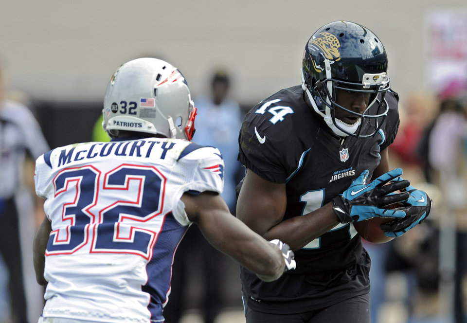 Photo - Jacksonville Jaguars wide receiver Justin Blackmon (14) catches a pass in the end zone in front of New England Patriots free safety Devin McCourty (32) for a touchdown during the first half of an NFL football game on Sunday, Dec.  23, 2012, in Jacksonville, Fla. (AP Photo/Stephen Morton)