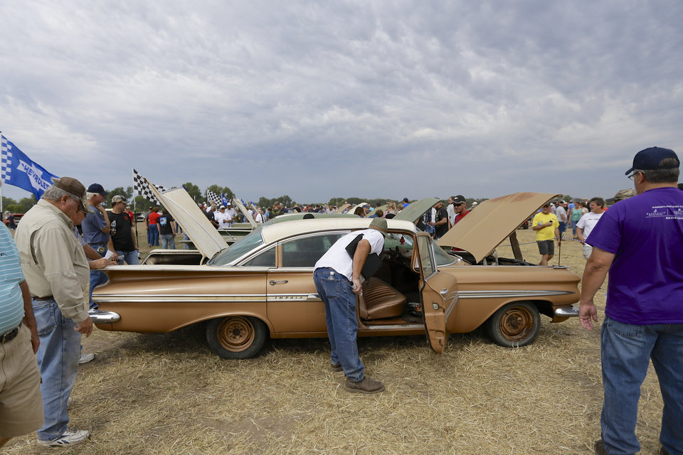 Photo - Car buffs survey a 1959 Chevrolet Impala, foreground, and other Chevrolet vehicles during a preview for an auction of vintage cars and trucks from the former Lambrecht Chevrolet dealership in Pierce, Neb., Friday Sept. 27, 2013. The auction takes place on Saturday and Sunday. (AP Photo/Nati Harnik)