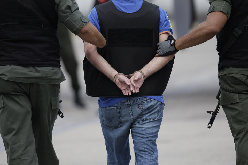 "Daniel Barrera Barrera, one of Colombia's most wanted drug lords, whose alias is ""El Loco Barrera,"" is escorted in handcuffs and a flak jacket by National Guard officers as he is deported to Colombia from the Simon Bolivar airport in Maiquetia, near Caracas, Venezuela, Wednesday, Nov. 14, 2012. Barrera was captured on Sept. 18 in San Cristobal, Venezuela, near the border with Colombia. (AP Photo/Ariana Cubillos)"