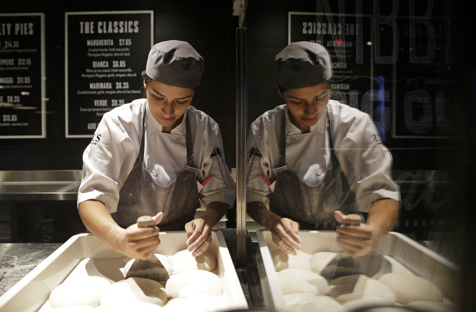 Photo - In this photo taken on Aug. 20, 2014, Kheyla Ramirez prepares pizza dough at 800 Degrees Pizza in the SLS Las Vegas in Las Vegas. The hotel and casino, formally known as the Sahara, has gone through extensive renovations is scheduled to open this weekend. (AP Photo/John Locher)