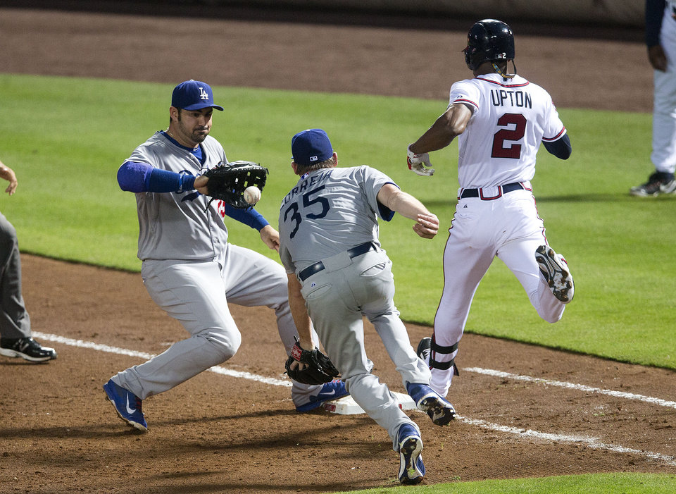 Photo - Los Angeles Dodgers pitcher Kevin Correia (35) flips the ball to first baseman Adrian Gonzalez (23) to force out Atlanta Braves' B.J. Upton (2) in the sixth inning of a baseball game  Monday, Aug. 11, 2014 in Atlanta.  (AP Photo/John Bazemore)