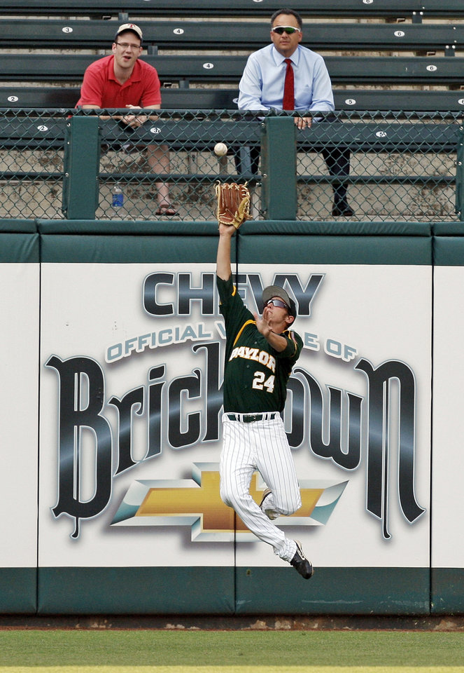 Photo - Baylor's Michael Howard (24) catches a fly ball during a Big 12 Baseball Championship tournament game between the Oklahoma Sooners and Baylor Bears at the Chickasaw Bricktown Ballpark in Oklahoma City,Thursday, May 24, 2012. OU won, 3-2. Photo by Nate Billings, The Oklahoman