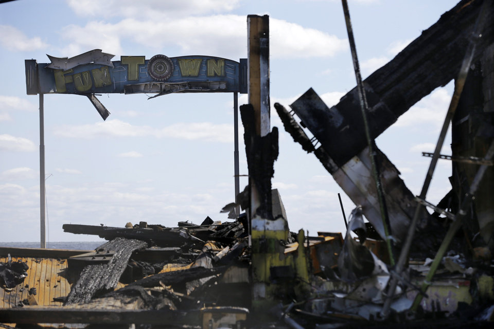 Photo - The sign for Funtown Pier stands above charred rubble in Seaside Park, N.J., Tuesday, Sept. 17, 2013, after a fire last Thursday that started near a frozen custard stand in Seaside Park,  quickly spread north into neighboring Seaside Heights. More than 50 businesses in the two towns were destroyed. The massive boardwalk fire in New Jersey began accidentally, the result of an electrical problem, an official briefed on the investigation said Tuesday. (AP Photo/Mel Evans)