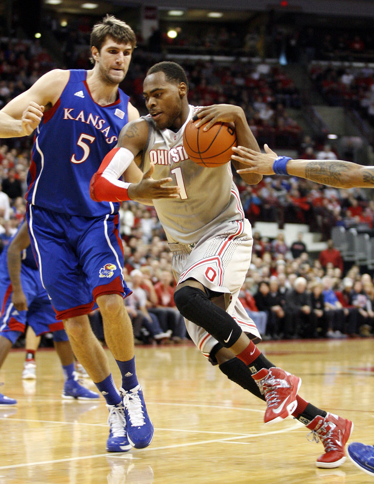 Ohio State's DeShaun Thomas (1) drives against Kansas' Jeff Withey (5) during the first half of an NCAA college basketball game Saturday, Dec. 22, 2012, in Columbus, Ohio. (AP Photo/Mike Munden)