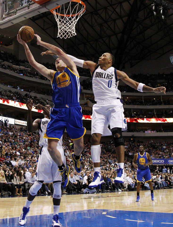 Dallas Mavericks forward Shawn Marion (0) defends against a shot by Golden State Warriors power forward David Lee (10) as Mavericks center Bernard James, bottom left, watches in the first half of an NBA basketball game, Monday, Nov. 19, 2012, in Dallas. (AP Photo/Tony Gutierrez)