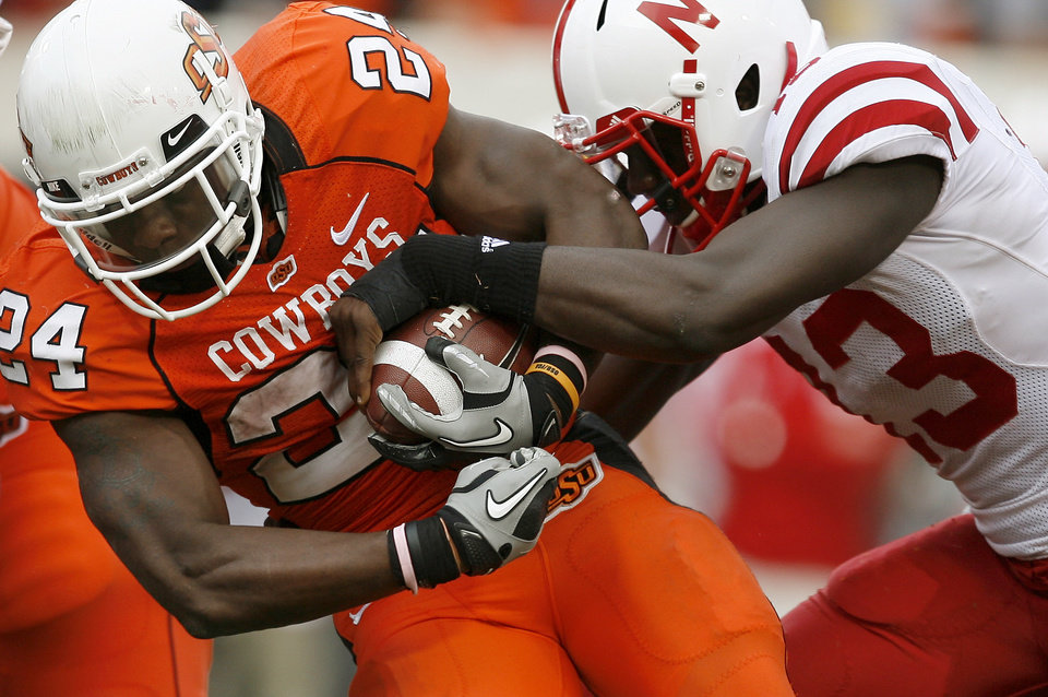 Photo - OSU's Kendall Hunter fights off Nebraska's P.J. Smith during the college football game between the Oklahoma State Cowboys (OSU) and the Nebraska Huskers (NU) at Boone Pickens Stadium in Stillwater, Okla., Saturday, Oct. 23, 2010. Photo by Bryan Terry, The Oklahoman