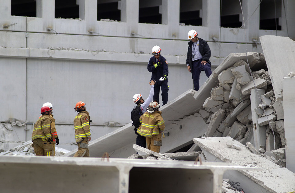 Photo -   Firefighters look over the rubble after a section of a parking garage under construction at a Miami-Dade College campus collapsed, Wednesday, Oct. 10, 2012 in Doral, Fla., killing one worker and trapping at least two others in the rubble, officials said. (AP Photo/J Pat Carter)