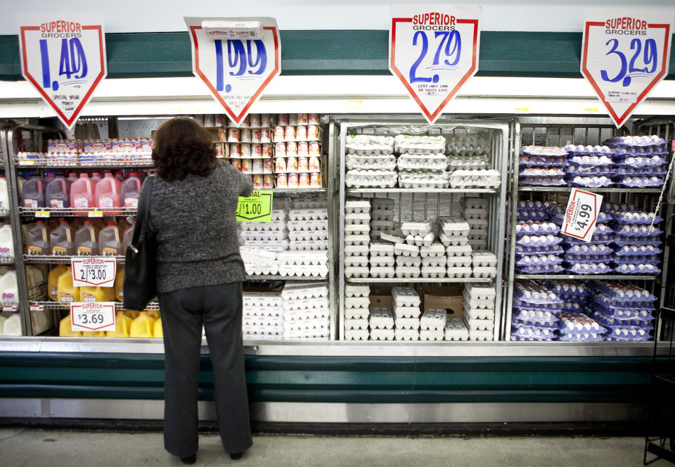 Photo - In this May 23, 2011 photo, a customer shops for dairy products at a Superior Grocers store in Los Angeles. Consumers paid more for food, cars and clothing in May, though overall consumer prices rose by the smallest amount in six months. (AP Photo/Damian Dovarganes) ORG XMIT: CADD303