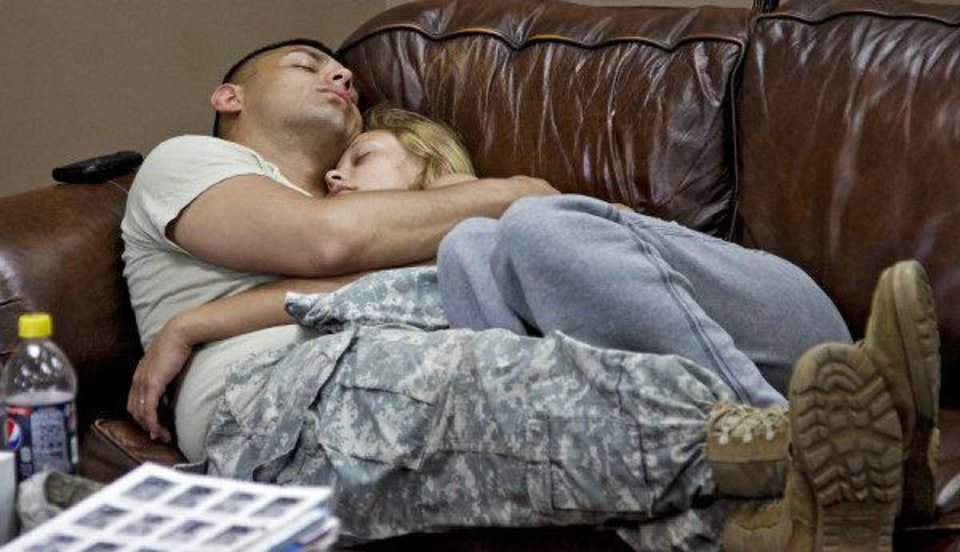 Photo - Brandon Hockersmith and his wife Shenay get in a quick nap while Brandon waits for his flight at the YMCA Military Welcome Center at Will Rogers World Airport.   CHRIS LANDSBERGER - CHRIS LANDSBERGER