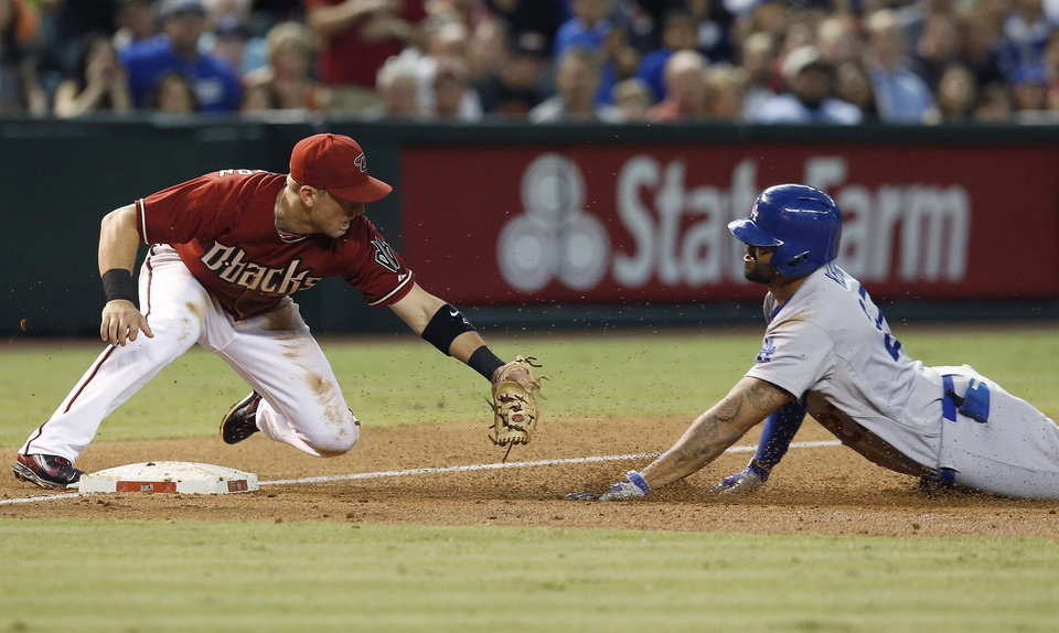 Photo - Arizona Diamondbacks' Cliff Pennington, left, waits to tag out Los Angeles Dodgers' Matt Kemp as Kemp slides into third base trying to stretch a double into a triple during the third inning of a baseball game Wednesday, Aug. 27, 2014, in Phoenix.  Kemp knocked in two runs on his double. (AP Photo/Ross D. Franklin)