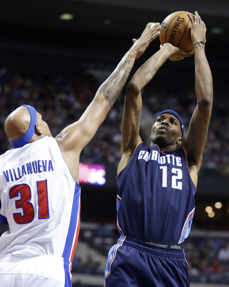 Photo - Charlotte Bobcats forward Tyrus Thomas (12) takes a shot against Detroit Pistons forward Charlie Villanueva (31) in the first half of an NBA basketball game, Sunday, Jan. 6, 2013, in Auburn Hills, Mich. (AP Photo/Duane Burleson)