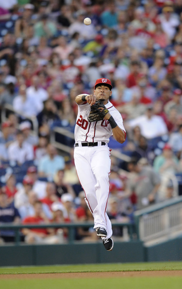 Washington Nationals shortstop Ian Desmond throws to first but is unable to get Colorado Rockies' Josh Rutledge out during the fifth inning of a baseball game, Friday, June 21, 2013, in Washington. Rutledge was ruled safe on the play. (AP Photo/Nick Wass)