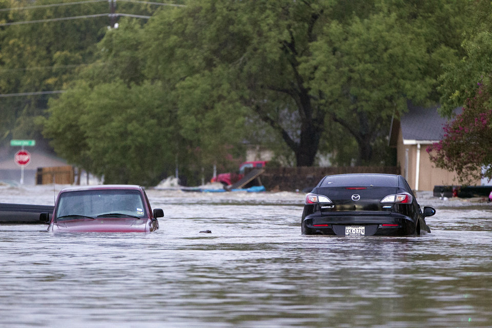 Photo - Cars are partially submerged on Quicksilver Blvd in southeast Austin, Texas, on Thursday, Oct. 31, 2013. Heavy overnight rains brought flooding to the area. The National Weather Service said more than a foot of rain fell in Central Texas, including up to 14 inches in Wimberley, since rainstorms began Wednesday.  (AP Photo/The Austin American-Statesman, Deborah Cannon) AUSTIN CHRONICLE OUT, COMMUNITY IMPACT OUT, INTERNET MUST CREDIT PHOTOGRAPHER AND STATESMAN.COM, NO SALES