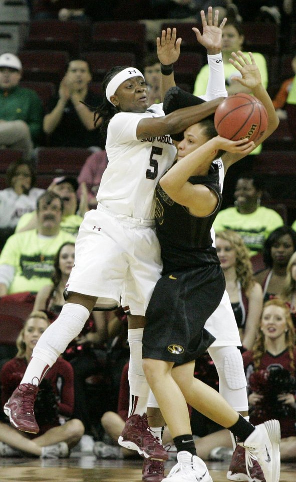 Photo - South Carolina's Khadijah Sessions (5) gets called for the foul as Missouri's Bri Kulas (13)  tries to move the ball during the second half of their NCAA college basketball game, Sunday Feb. 2, 2014, in Columbia, SC. (AP Photo/Mary Ann Chastain)