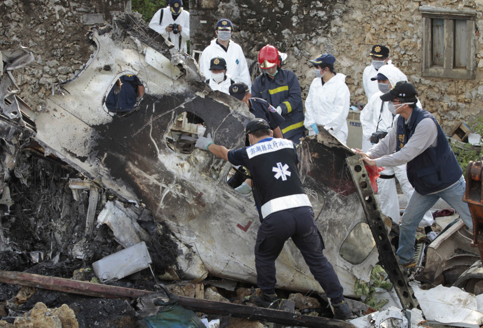 Photo - A forensic team recovers human remains among the wreckage of crashed TransAsia Airways flight GE222 on the outlying island of Penghu, Taiwan, Thursday, July 24, 2014. Stormy weather on the trailing edge of Typhoon Matmo was the likely cause of the plane crash that killed more than 40 people, the airline said. Aviation has suffered one of its worst weeks in memory, a cluster of disasters spanning three continents. (AP Photo/Wally Santana)