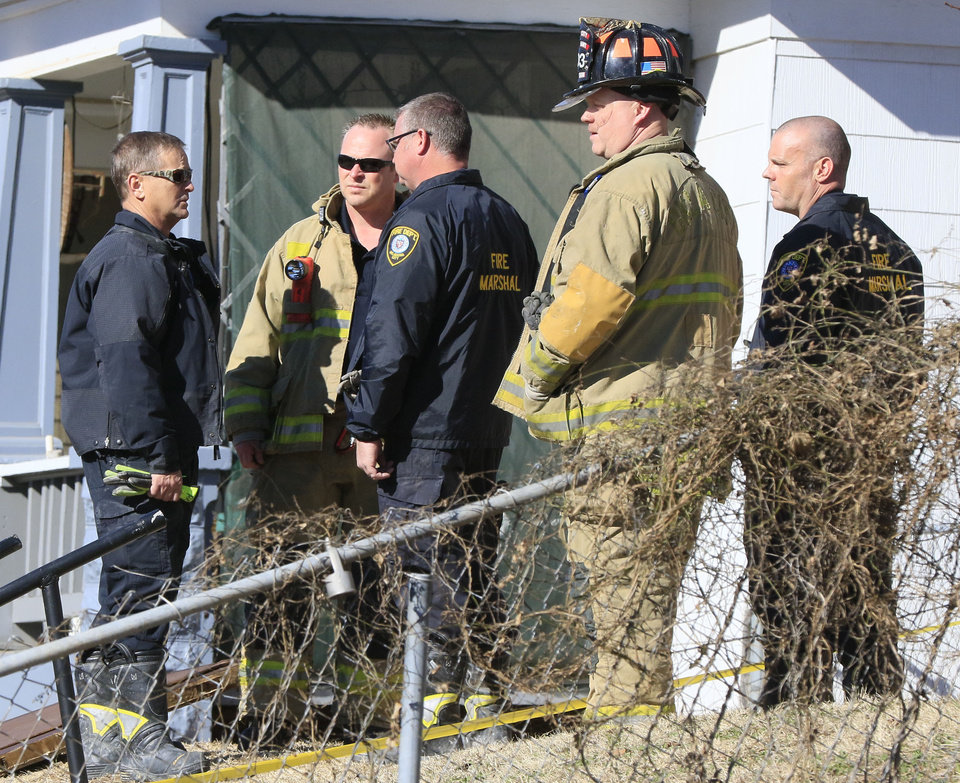 Photo -  Oklahoma City Police and Fire Dept. officials investigate the scene where a woman was found dead inside a duplex in the 1800 block of NW 9th St in Oklahoma City on Friday. [Photo by Paul Hellstern, The Oklahoman]