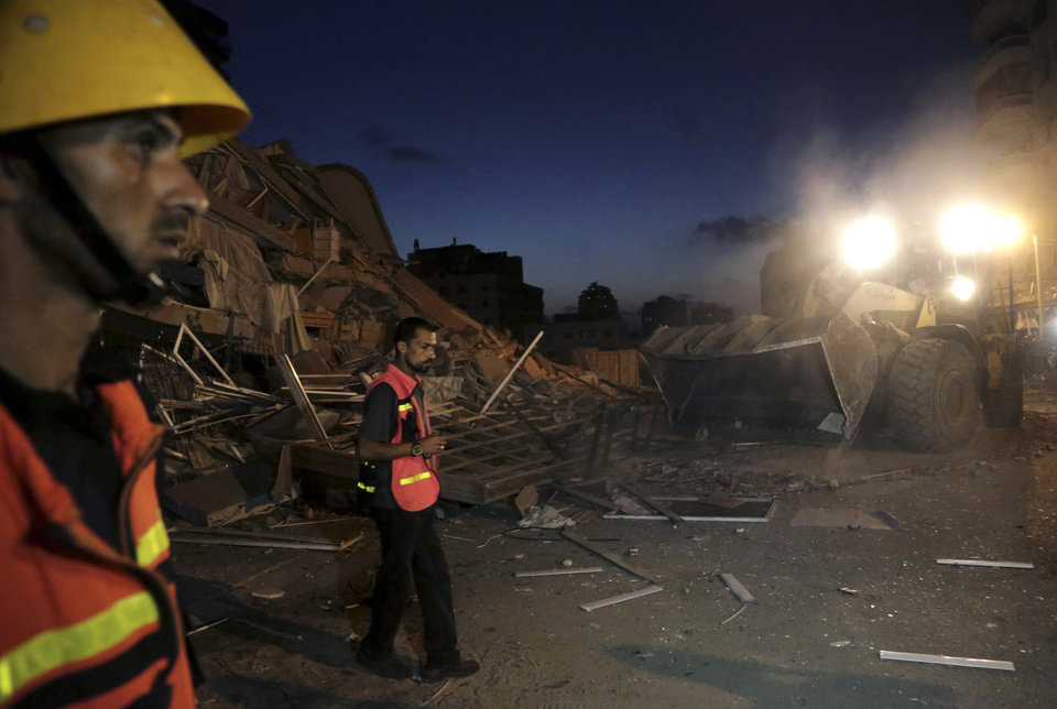 Photo - Palestinian firefighters work to reopen a main road in front of the rubble of al-Zafer apartment tower following an Israeli airstrikes in Gaza City, in the northern Gaza Strip, Saturday, Aug. 23, 2014. Israeli aircraft fired two missiles at a 12-story apartment tower in downtown Gaza City on Saturday, collapsing the building, sending a huge fireball into the sky and wounding at least 22 people, including 11 children, witnesses and Palestinian officials said. (AP Photo/Adel Hana)