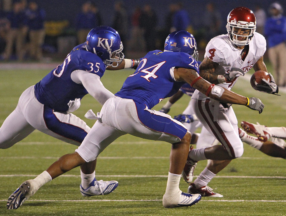 Photo - Oklahoma's Kenny Stills (4) tries to get by Kansas' Toben Opurum (35) and Bradle McDougald (24) during the college football game between the University of Oklahoma Sooners (OU) and the University of Kansas Jayhawks (KU) on Sunday, Oct. 16, 2011. in Lawrence, Kan. Photo by Chris Landsberger, The Oklahoman