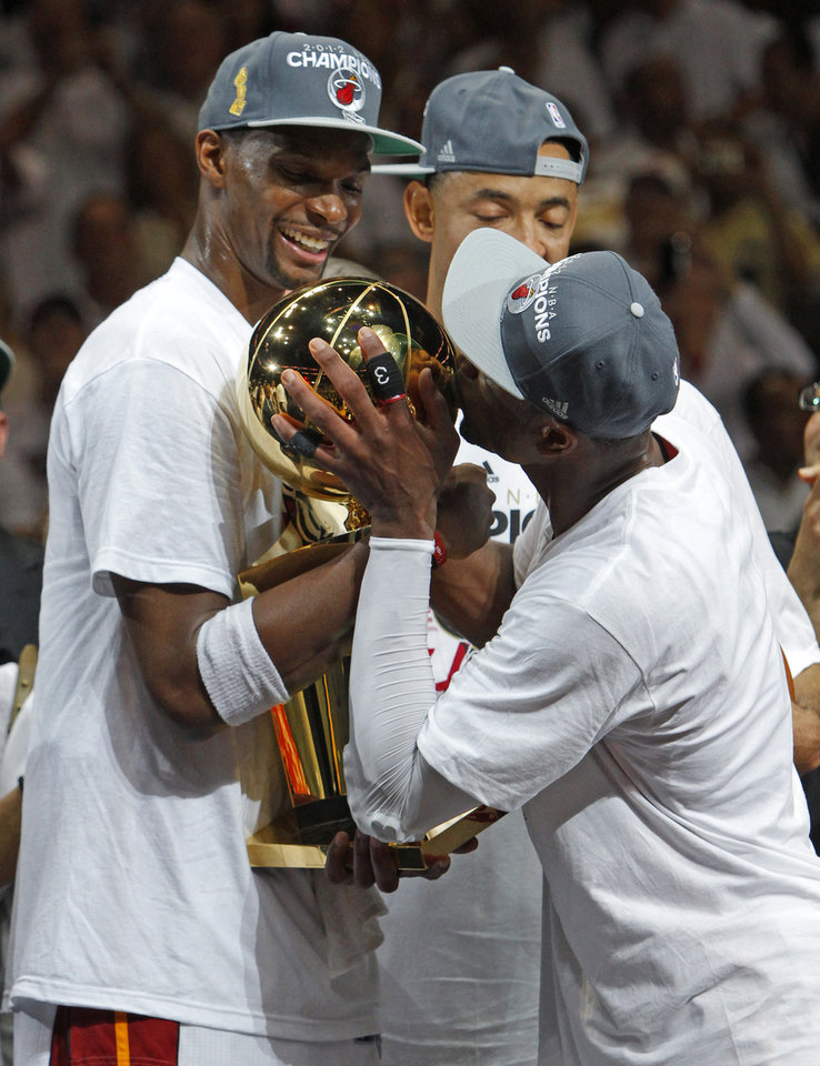 Miami's Dwyane Wade, at right, and Chris Bosh celebrate with the Larry O'Brien NBA Championship Trophy after Game 5 of the NBA Finals between the Oklahoma City Thunder and the Miami Heat at American Airlines Arena, Thursday, June 21, 2012. Oklahoma City lost 121-106. Photo by Bryan Terry, The Oklahoman
