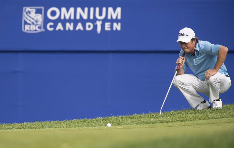 Photo - Tim Clark, of South Africa, lines up a putt on the 18th green during the third round of the Canadian Open golf championship at the Royal Montreal Golf Club in Montreal, Saturday, July 26, 2014. (AP Photo/The Canadian Press, Graham Hughes)