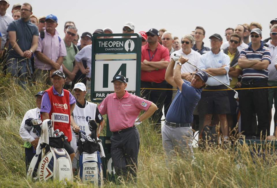 Photo - Phil Mickelson of the US plays a shot off the 14th tee as Ernie Els of South Africa, second right, looks along the fairway during the second day of the British Open Golf championship at the Royal Liverpool golf club, Hoylake, England, Friday July 18, 2014. (AP Photo/Peter Morrison)