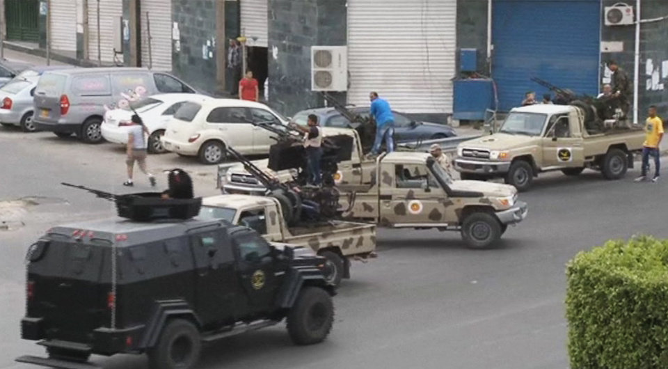Photo - In this image made from video provided by the Libyan national army via AP Television, Tripoli joint security forces on vehicles with heavy artillery stand guard on the entrance road to the parliament area after troops of Gen. Khalifa Hifter targeted Islamist lawmakers and officials at the parliament in Tripoli, Libya, Sunday, May 18, 2014. Forces loyal to a rogue Libyan general attacked the country's parliament Sunday, expanding his eastern offensive against Islamists into the heart of the country's capital. (AP Photo/Libyan national army)