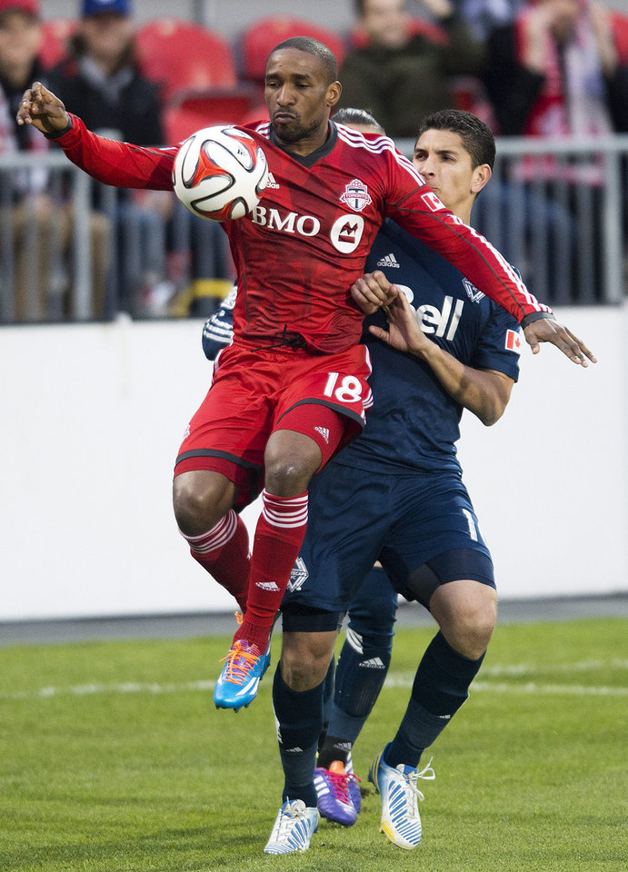 Photo - Toronto FC forward Jermain Defoe, left, battles for the ball against Vancouver Whitecaps defender Johnny Leveron, right, during first half semi-final Amway Canadian Championship soccer action in Toronto on Wednesday, May 7, 2014. (AP Photo/The Canadian Press, Nathan Denette)