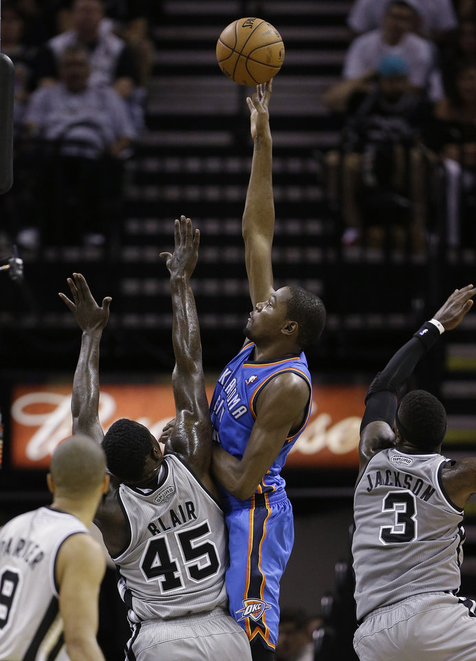 Oklahoma Thunder's Kevin Durant, center, scores over San antonio Spurs' DeJuan Blair (45) during the second quarter of an NBA basketball game, Thursday, Nov. 1, 2012, in San Antonio. (AP Photo/Eric Gay) ORG XMIT: TXEG107