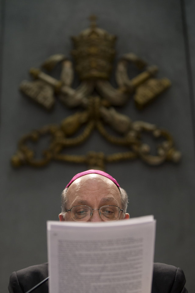 Photo - Archbishop Pier Luigi Celata, Vice Chamberlain, reads a copy of a document signed by Pope Benedict XVI, a press conference, at the Vatican, Monday, Feb. 25, 2013. Pope Benedict XVI has changed the rules of the conclave that will elect his successor, allowing cardinals to move up the start date if all of them arrive in Rome before the usual 15-day transition between pontificates. Benedict signed a legal document, issued Monday, with some line-by-line changes to the 1996 Vatican law governing the election of a new pope. It is one of his last acts as pope before resigning Thursday.  (AP Photo/Andrew Medichini)