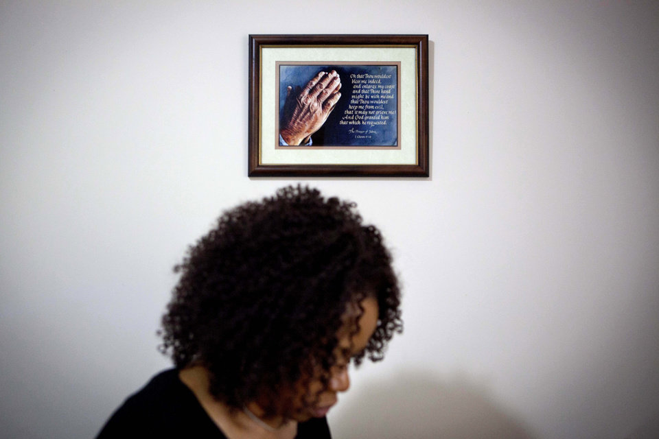 Photo -   A prayer hangs on the wall as Patricia Jackson sifts through bank documents in her home Saturday, June 16, 2012, in Marietta, Ga. On a suburban cul-de-sac northwest of Atlanta, the Jacksons are struggling to keep a house worth $100,000 less than they owe. Their voices and those of many others tell the story of a country that, for all the economic turmoil of the past few years, continues to believe things will get better. But until it does, families are trying to hang on to what they've got left. The Great Recession claimed nearly 40 percent of Americans' wealth, the Federal Reserve reported last week. The new figures, showing Americans' net worth has plunged back to what it was in 1992, left economists shuddering. (AP Photo/David Goldman)