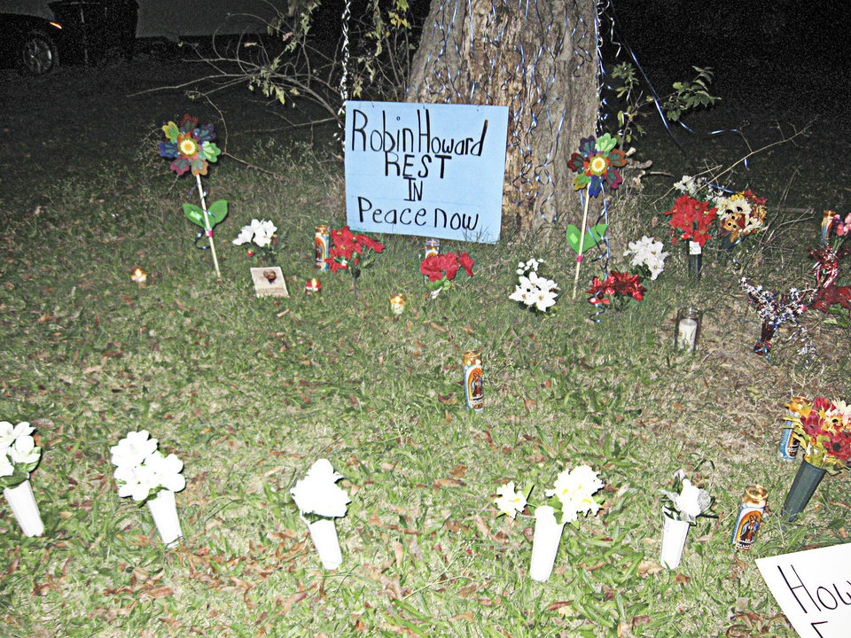 A makeshift for Robin Leander Howard at the base of a tree in the 1400 block of Monticello Court.  A candelight vigil honoring his life was held there Sunday night. <strong>MATT DINGER</strong>