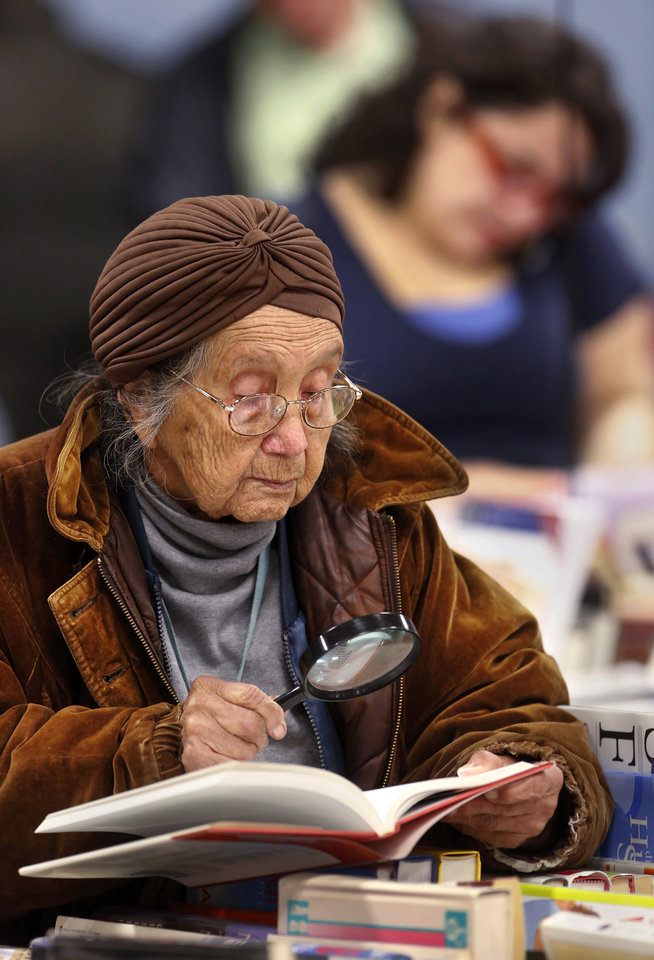 Ruth Brown, 92, brought a magnifying glass to the sale to help her read the small print as she searched for books on health, healing and meditation. Several thousand bibliophiles and bargain hunters crowded into Oklahoma Expo Hall at State Fair Park on Saturday, Feb. 23, 2013, in a quest to find reading material at deeply discounted prices. Friends of the Metropolitan Library System is holding their much-anticipated annual book sale this weekend. The sale continues Sunday from 9 a.m. to 5:30 p.m. Photo by Jim Beckel, The Oklahoman