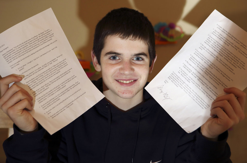 In this Jan. 4, 2013, photo, Gregory Hofmann poses with a signed contract at his home in Sandwich, Mass. Hofmann's mother Janell drafted the contract which outlines conditions for his use of his first Apple iPhone. (AP Photo/Michael Dwyer)