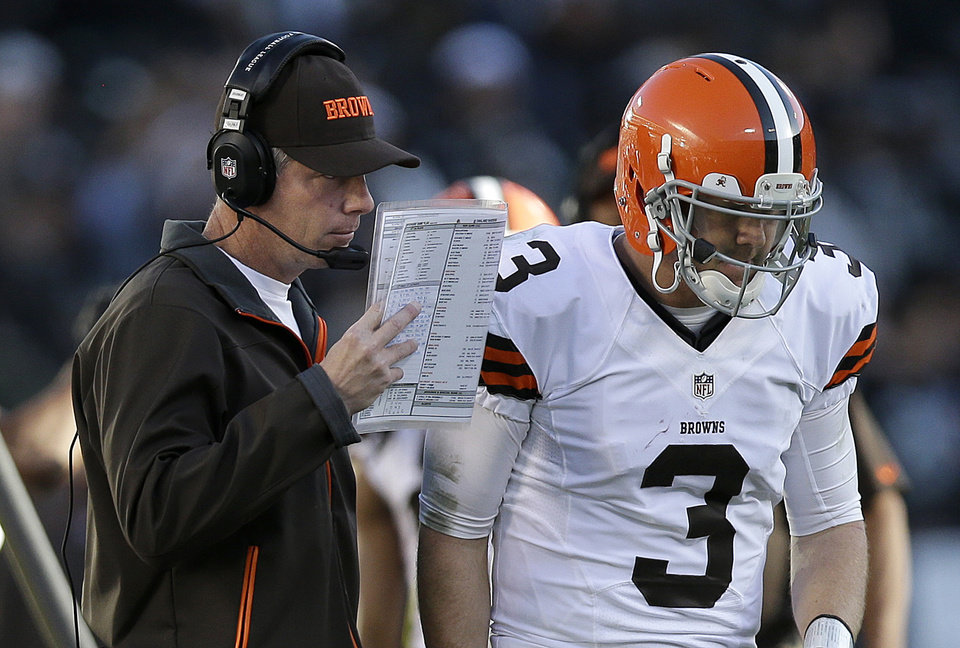 Photo - Cleveland Browns head coach Pat Shurmur, left, talks with quarterback Brandon Weeden (3) during the second half of an NFL football game against the Oakland Raiders in Oakland, Calif., Sunday, Dec. 2, 2012. (AP Photo/Marcio Jose Sanchez)