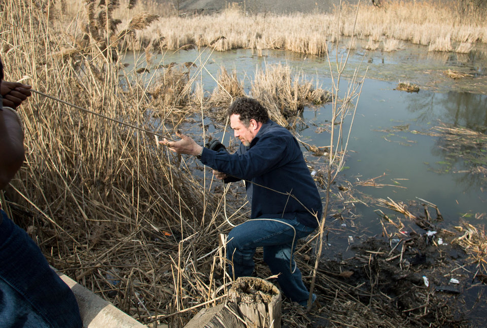Photo - Beduareo Marquez climbs up the pond embankment where he retrieved a shoe from the crash site that six teens died on Park Ave. in Warren, Ohio on Sunday, March 10, 2013. (AP Photo/Scott R. Galvin)