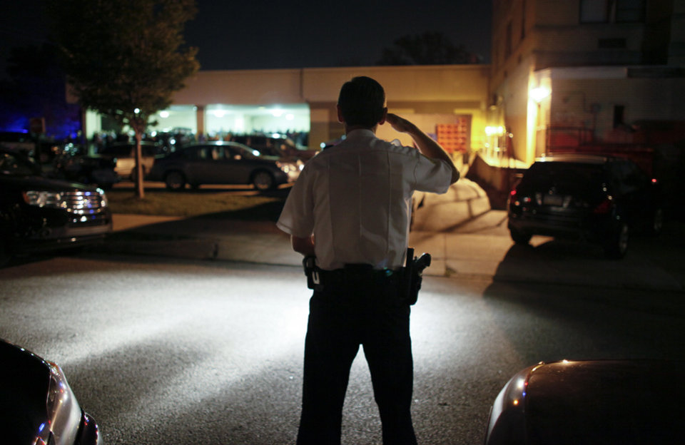 Photo -   A Police officer salutes as the body of slain Plymouth Township canine officer Brad Fox, on Thursday, Sept. 13, 2012, is taken from Montgomery Hospital in Norristown Pa. The officer was shot and killed while responding to a hit-and-run in a Philadelphia suburb, authorities said. (AP Photo/Joseph Kaczmarek)