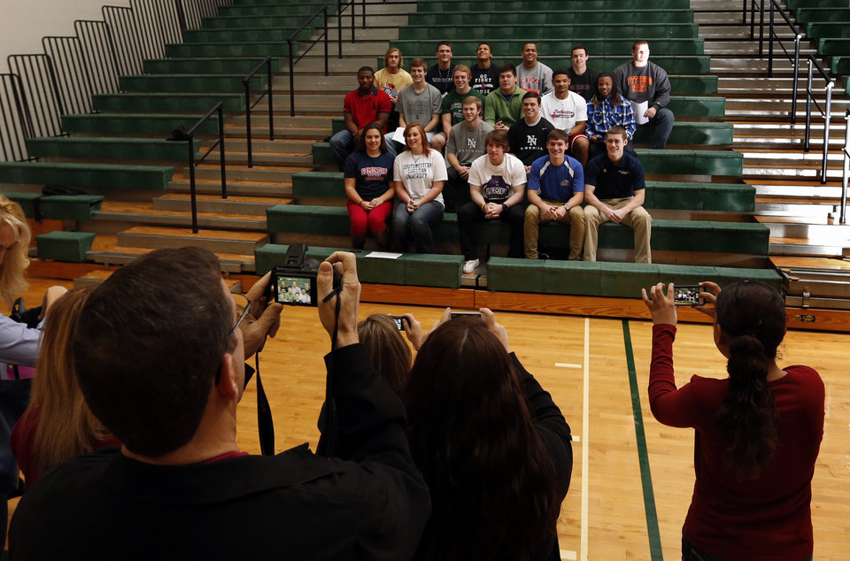 Photo - Parents, siblings and friends take photographs of  senior athletes at a signing day assembly at Norman North High School on Wednesday, Feb. 6, 2013, in Norman, Okla.  Photo by Steve Sisney, The Oklahoman