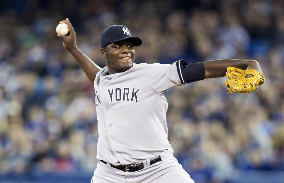 Photo - New York Yankees starting pitcher Michael Pineda throws during the first inning of a baseball game in Toronto on Saturday, April 5, 2014. (AP Photo/The Canadian Press, Peter Power)