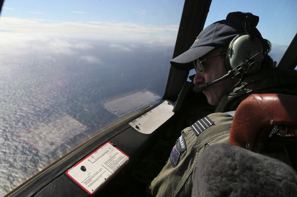 Photo - Royal New Zealand Air Force P-3 Orion's captain, Wing Comdr. Rob Shearer watches out of the window of his aircraft while searching for the missing Malaysia Airlines Flight MH370 in the southern Indian Ocean, Monday, March 31, 2014. (AP Photo/Rob Griffith, Pool)