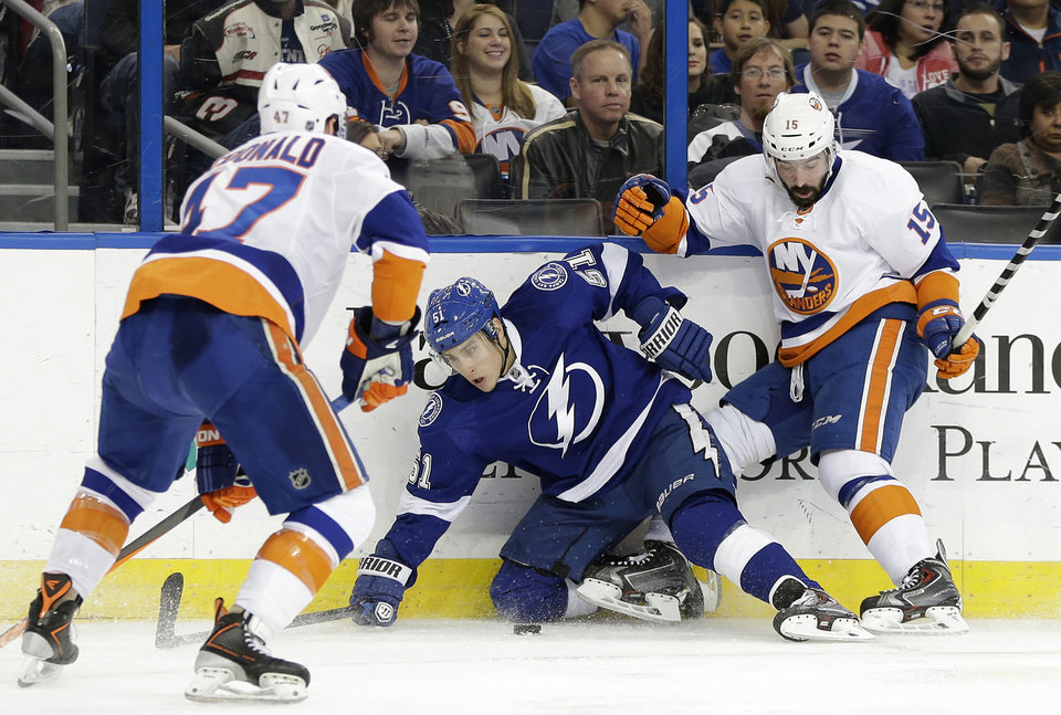 Photo - New York Islanders right wing Cal Clutterbuck (15) takes down Tampa Bay Lightning center Valtteri Filppula (51), of Finland, in front of Islanders defenseman Andrew MacDonald (47) during the second period of an NHL hockey game, Thursday, Jan. 16, 2014, in Tampa, Fla. (AP Photo/Chris O'Meara)