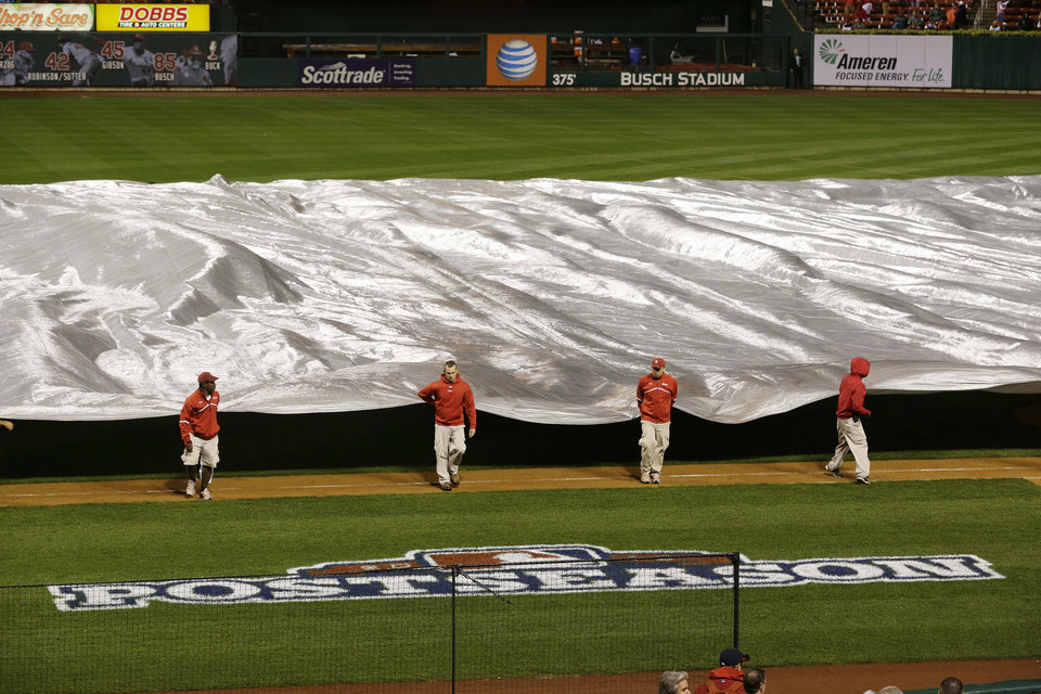 Photo -   Ground crew takes tarp of of the field to prepare during the rain delay of Game 3 of baseball's National League championship series between the St. Louis Cardinals and the San Francisco Giants Wednesday, Oct. 17, 2012, in St. Louis. (AP Photo/Patrick Semansky)