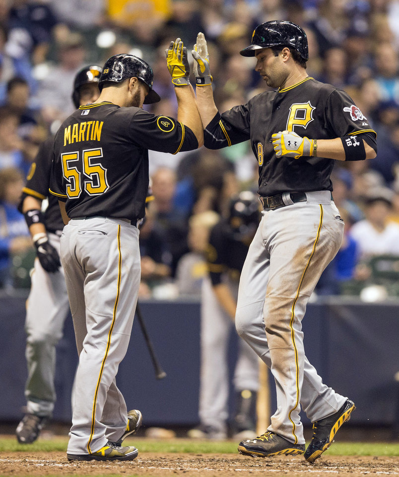 Photo - Pittsburgh Pirates' Neil Walker, right, is greeted by teammate  Russell Martin after hitting a two-run home run off Milwaukee Brewers' Wily Peralta during the seventh inning of a baseball game on Friday, April 11, 2014, in Milwaukee. (AP Photo/Tom Lynn)