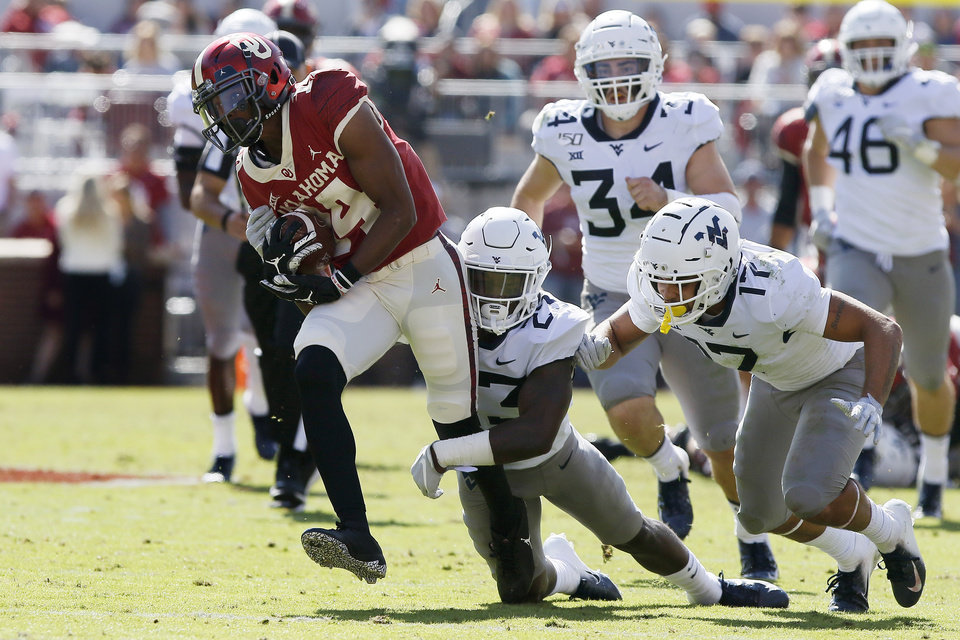Photo - Oklahoma's Charleston Rambo (14) is brought down by West Virginia's Tykee Smith (23) and Exree Loe (17) during a college football game between the University of Oklahoma Sooners (OU) and the West Virginia Mountaineers at Gaylord Family-Oklahoma Memorial Stadium in Norman, Okla, Saturday, Oct. 19, 2019. Oklahoma won 52-14. [Bryan Terry/The Oklahoman]