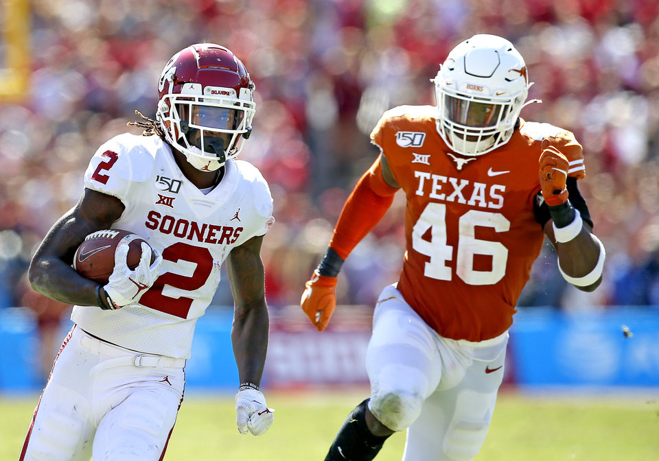 Photo - Oklahoma's CeeDee Lamb (2) runs after a catch as Texas linebacker Joseph Ossai (46) chases him in the second quarter during the Red River Showdown college football game between the University of Oklahoma Sooners (OU) and the Texas Longhorns (UT) at Cotton Bowl Stadium in Dallas, Saturday, Oct. 12, 2019. OU won 34-27. [Sarah Phipps/The Oklahoman]