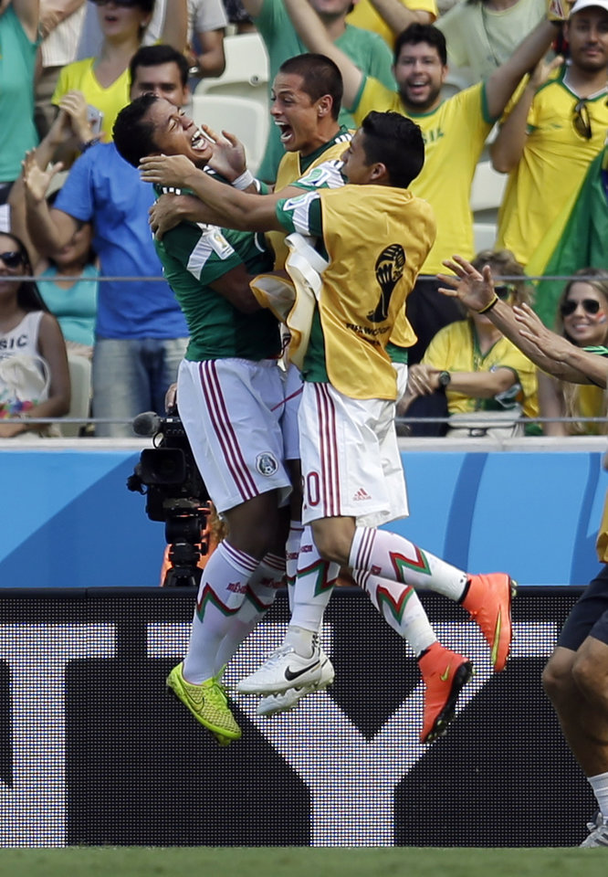 Photo - Mexico's Giovani dos Santos, left, celebrates after scoring the opening goal during the World Cup round of 16 soccer match between the Netherlands and Mexico at the Arena Castelao in Fortaleza, Brazil, Sunday, June 29, 2014. (AP Photo/Natacha Pisarenko)