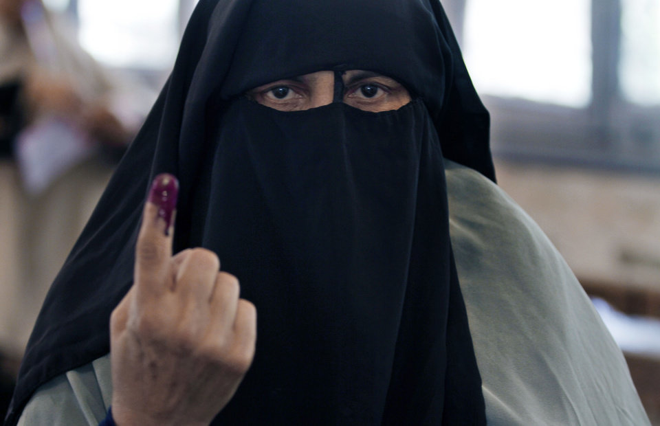 Photo -   An Egyptian woman shows her inked after casting her vote during the first day of the presidential election in a polling station in Alexandria, Egypt, Wednesday, May 23, 2012. Egyptians went to the polls on Wednesday morning to elect a new president after the fall of ex-President Hosni Mubarak last year. (AP Photo/Khalil Hamra)