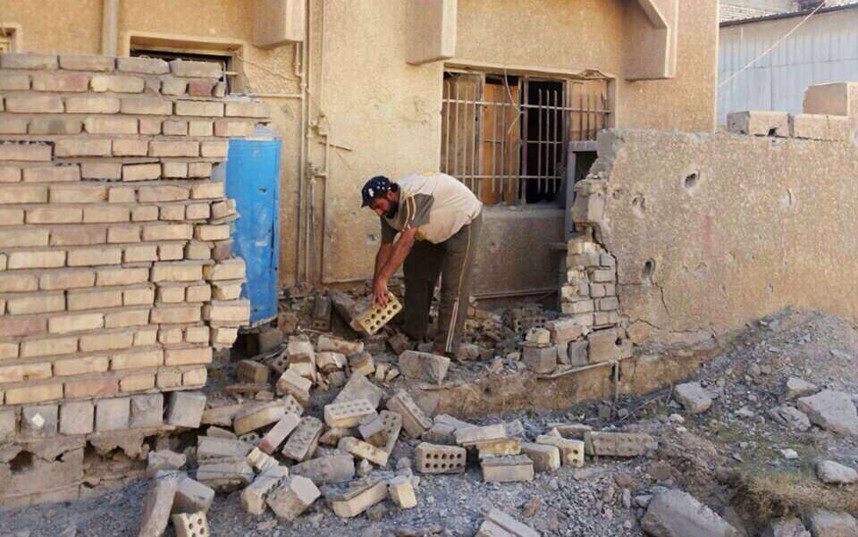 Photo - Abu Rasool al-Kubaisi clears debris at his home after a bombing in Fallujah, 40 miles (65 kilometers) west of Baghdad, Iraq, Sunday, June 22, 2014. Sunni militants have seized another town in Iraq's western Anbar province, the fourth to fall in two days, officials said Sunday, in what is shaping up to be a major offensive in one of Iraq's most restive regions. (AP Photo)