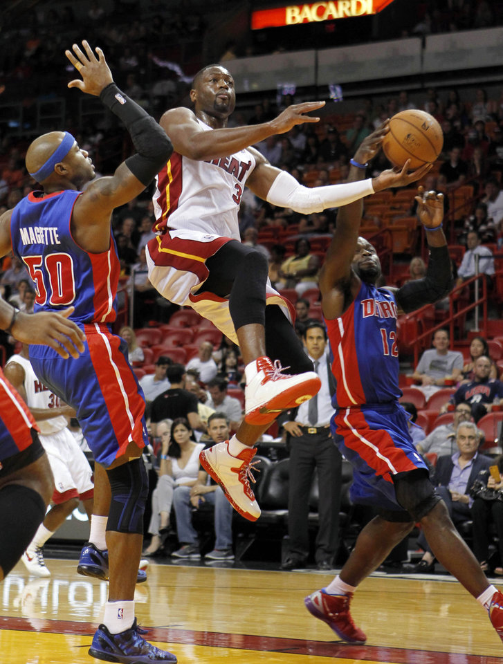 Photo -   Miami Heat's Dwyane Wade (3) goes to the basket as Detroit Pistons' Will Bynum (12) blocks and Detroit Pistons' Greg Monroe (10) defends during the first half of a preseason NBA basketball game in Miami, Thursday, Oct. 18, 2012. (AP Photo/Alan Diaz)
