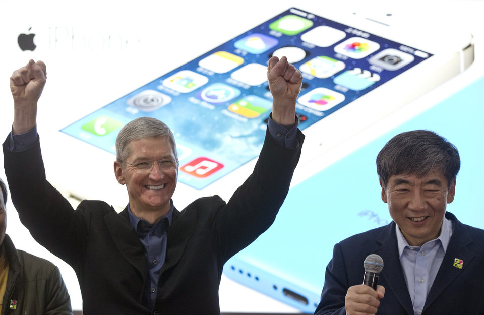 Photo - FILE - In this Jan. 17, 2014 file photo, Apple's CEO Tim Cook, left, gestures as China Mobile Chairman Xi Guohua smiles during a promotional event that marks the opening day of sales of China Mobile's 4G iPhone 5s and iPhone 5c in Beijing, China. Soaring sales of iPhones in China, Russia, India and Brazil during the April-June 2014 period helped Apple overcome softening demand for the device in the U.S. and Europe, where consumers seem to be more interested in waiting for the autumn release of a new iPhone that's expected to feature a larger screen. (AP Photo/Alexander F. Yuan, File)